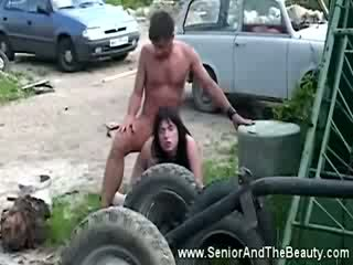 Busty brunette gets fucked against an old car by antique dude