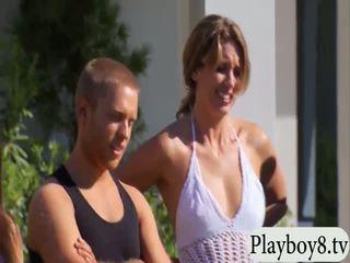 กลุ่ม ของ swinging couples การเล่น ด้วย น้ำ guns outdoors
