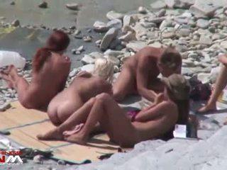 שלוש עירום חוף couples enjoying casual נקבה בלבוש וגברים עירומים ביחד