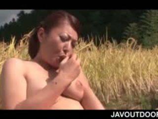 Rijpere aziatisch hottie neuken haarzelf met een speelbal op een veld