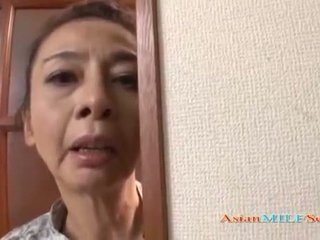 Eldre asiatisk kvinne i en tanga sucks en pikk
