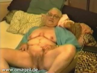Old Granny With Glasses Lying On A Bed In A Bathrobe
