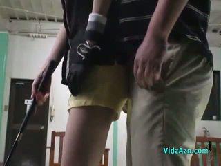 Aziatisch meisje giving pijpen op haar knees voor haar golf instructor