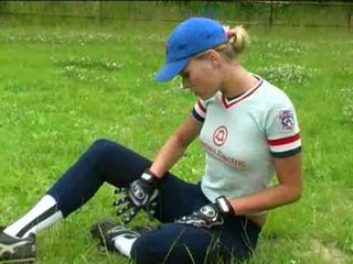 Taking off her baseball uniform