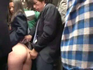 Skolejente famlet av stranger i en crowded buss