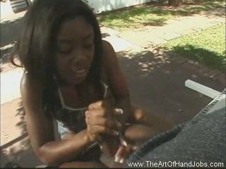 African chick giving her bf a handjob outdoors..