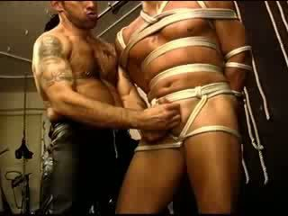 Muscle hunk is suspended with an electro anal probe up his big booty while top squeezes his balls.