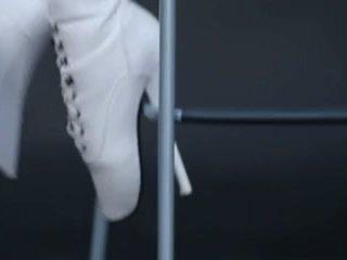 मॉडेल में लेटेक्स कॉट्स्यूट और ballet बूट्स.