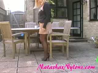 家庭主婦 在 棕色 絲襪 stiletto 高 腳跟 和 mini 裙子
